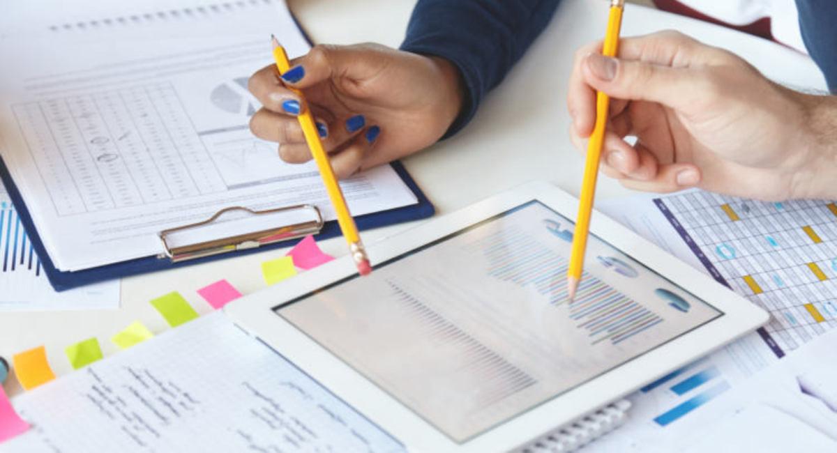 2 Personen arbeiten in einem Start-up zusammen an CRM Kundnanalyse Report Neukundengewinnung. Sie nutzen Tablet mit Diagrammen